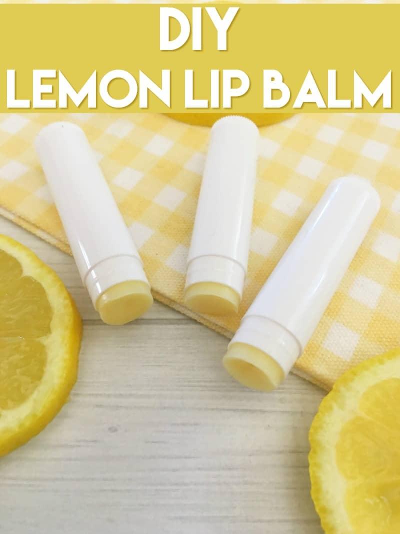 White tubes of homemade lemon lip balm on a yellow checkered towel and lemon slices